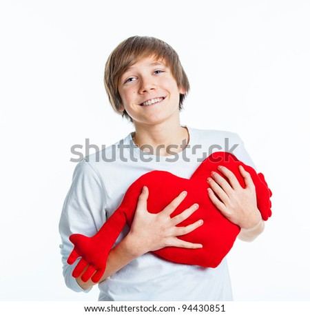 A cute young boy in love with a red plush heart in his hands. isolated