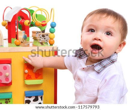 A cute young boy playing with his colorful toys isolated over white