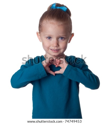 A cute young child forms the shape of a heart in her hands.