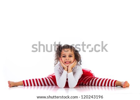 A cute young girl doing the splits and resting her chin on her hands.