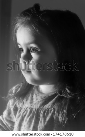 A cute young girl is looking television.She is looking very interested in.Oicture is black and white.