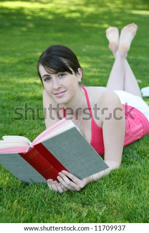 A cute young girl reading a book in the grass