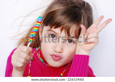 A cute young girl with a sucker giving a peace sign