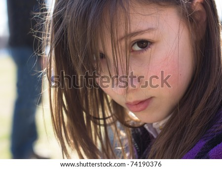 A cute young girl with an worried expression and a figure lurking behind her
