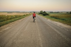 A cyclist in a red T-shirt is driving along the road to the horizon in the field.Speed.Desire to move forward.Rdingacross the field