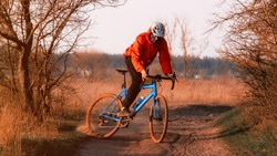 A cyclist on a gravel bike rides along the road raising dust from the rear wheel at sunset. Gravel biking. Extreme sports and activity concept.