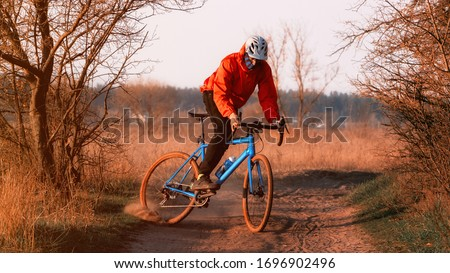 Photo of  A cyclist on a gravel bike rides along the road raising dust from the rear wheel at sunset. Gravel biking. Extreme sports and activity concept.