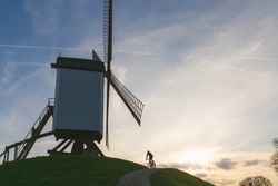 A cyclist rides by a traditional windmills in Park Kruisvest on a sunny autumn day in Bruges, Belgium