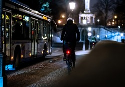 A cyclist riding alongside the bus in the illuminated city at night