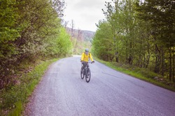 A cyclist with a yellow shirt rides bike lonely on a jungle road.