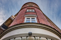 A cylindrical, brick made and classical building facade with windows in the middle of it. House rounded modern exterior with red bricks represents the noeclassical Swedish architecture - Malmo, Sweden