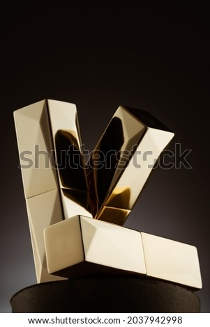 A 3D rendering of three golden prisms forming the letter K on a black background Stock fotó ©