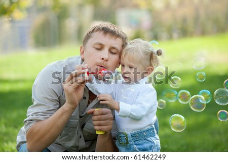 A dad and his daughter are making bubbles in the park