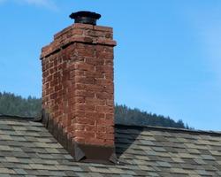 A damaged brick chimney on a blue sky
