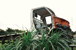 a damaged cargo van left on a pile of grass in a junkyard of automobiles waiting to be destroyed or recycled