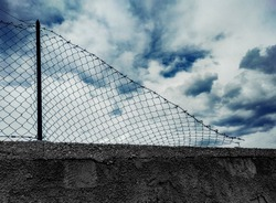 A damaged chainlink fence, with barbed wire on top, installed on a grim gray wall, showing a cloudy but blue sky over it. Symbolic shot: freedom, prison, war, hope, escape.