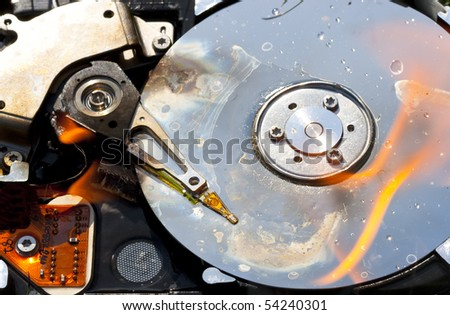 a damaged hard disk with fire - stock photo
