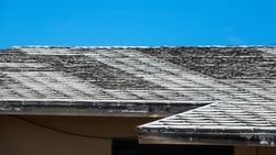 A damaged shingles roof on a blue sky
