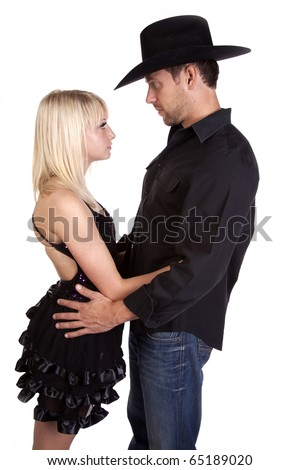 A dancer and her cowboy looking deep into each others eyes with serious expressions on their faces.