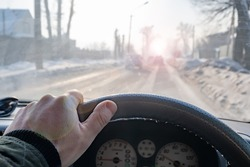 a dangerous road, a man's hand on the steering wheel of a car that is driving on a snow covered slippery icy winter road and the sun's glare impairs the visibility of the path, blinding the eyes