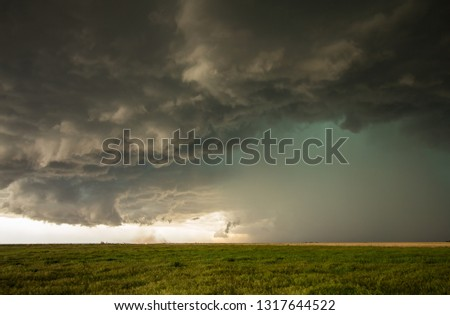 A dangerous supercell storm containing torrential rain and large hail emits a green glow in the sky. #1317644522