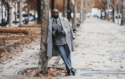 A dapper black senior entrepreneur in eyeglasses and an elegant outfit with a custom-made costume and a coat, is leaning against a tree on an autumn boulevard alleyway; a copy space place on the right