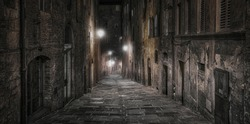 A dark and narrow alleyway in the medieval city of Siena at night with streetlights in the background - Siena, Tuscany, Italy
