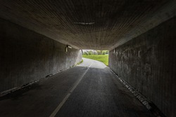A dark bike underpass with a curve in the end of the tunnel.