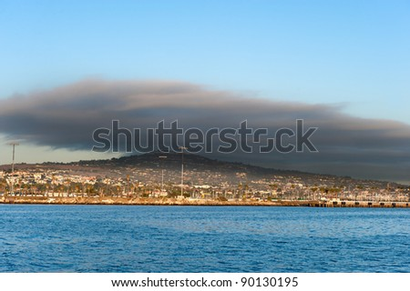 A dark cloud hangs over an upper scale community behind an oceanfront wharf.