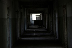 A dark corridor in an abandoned building. A cluttered corridor in ruins. Abandoned building. Horror. Dark room. Long passage.