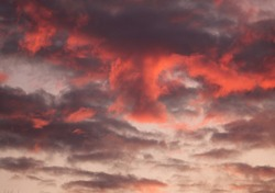 A dark gray and reddish-pink billowy cloud with a cone shape flowing from it and gray and light gray fluffs of clouds scattered across a grayish -white sky.