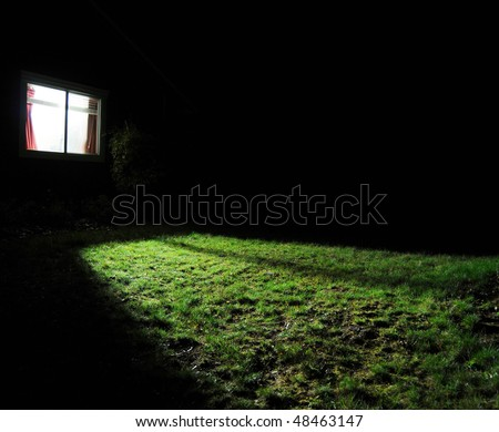 A dark house at night with a window with a light on in the room spilling out light onto the grass lawn yard