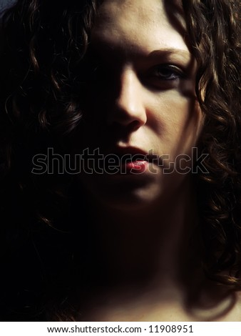 A dark low-key portrait about a pretty lady with white skin and long brown wavy hair whose look is attractive