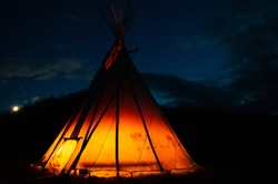 A dark night background with a tipi glowing orange from a fire inside.