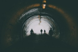 A dark pedestrian tunnel is in city. Silhouettes of going people.