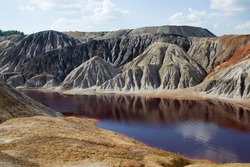 A dark red, acidic river against the backdrop of clay hills, a blue sky with clouds and a green forest. Hills and sky are reflected in the surface of the water.