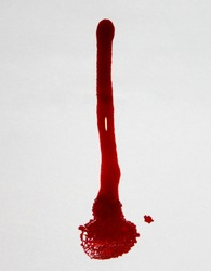 A dark red liquid dye/ink spill on a white surface; a blood drip design on a white background.