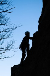 A dark silhouette of a rock climber climbing up a cliff on the background of blue sky and tree branches.