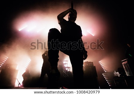 A dark silhouette of a singer on the stage. Good-looking background, bright stag lights. A concert of a famous music band