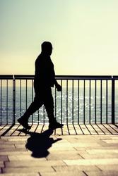 A dark silhouette of an unrecognizable man walking along a beach promenade at summer sunrise
