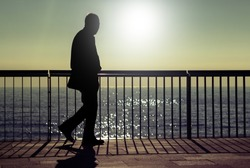 A dark silhouette of an unrecognizable man walking along a beach promenade in summer sunrise