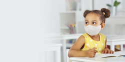 A dark-skinned girl in a medical mask for respiratory protection in a yellow dress listens attentively to the teacher. white background. Banner format