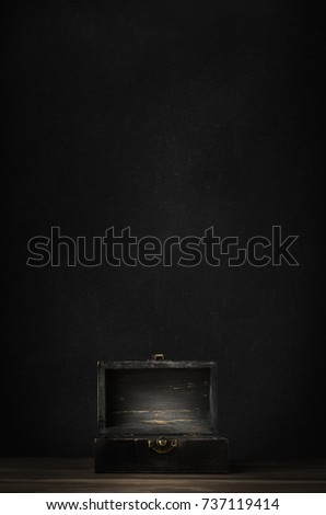 A dark wooden treasure chest with lid open and lit on planked surface with black chalkboard background. #737119414
