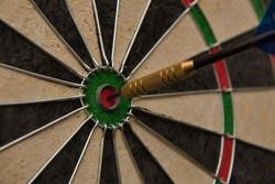 A dart hits the center of the darts board also known as