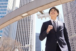 A dashing Japanese businessman walks in the office district.