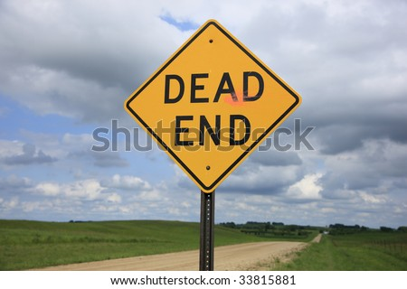 A Dead End sign posted along a rural gravel road.