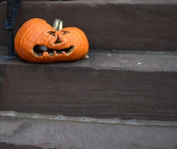 A decaying jack o lantern sits forlornly on the stairs of a Brooklyn brownstone, as if its distorted face is melting.
