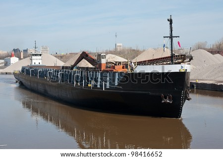 A deck barge powered by a tugboat moves up the Cuyahoga River in Cleveland, Ohio past mounds of aggregate material used to make concrete
