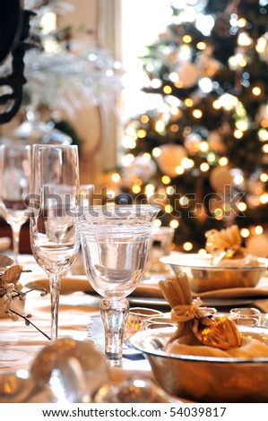 A decorated christmas dining table with wine glasses and christmas tree in background