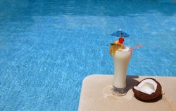 A decorated cocktail (Pina Colada) on the swimming pool border - Lifestyle concept